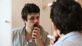 Capelli facciali di rasatura a macchina Rasatura asciutta del giovane uomo sonnolento con il regolatore elettrico video d archivio