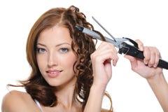 Capelli femminili d'arricciatura del brunette con il rullo immagine stock