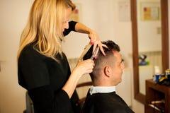 Capelli femminili di taglio del parrucchiere del cliente sorridente dell'uomo a bellezza immagini stock