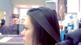 Capelli marroni scuri degli straights del parrucchiere di bella donna che utilizza le tenaglie dei capelli nel salone di bellezza stock footage