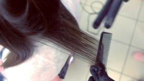 Capelli marroni scuri degli straights del parrucchiere di bella donna che utilizza le tenaglie dei capelli nel salone di bellezza video d archivio