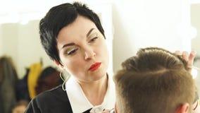 Capelli maschii di taglio dello stilista della donna con il tagliatore ed il pettine nel negozio di barbiere Affronti la donna ch video d archivio