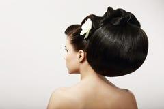 Capelli neri sani lisci con il fiore. Salone della stazione termale fotografie stock