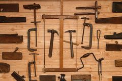 Ancient Carpenter Tools on a wooden wall Stock Photography