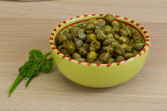 Capers. In the bowl with green leaves Stock Photos