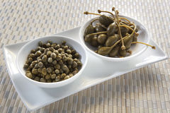 Capers and Caper Berries. Small white bowls of capers and caper berries Royalty Free Stock Photos