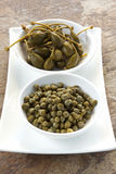 Capers and Caper Berries. In small white bowls over stone background Royalty Free Stock Images