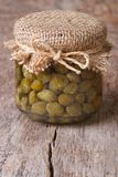 Capers in a glass jar on the old table, close-up Royalty Free Stock Photo