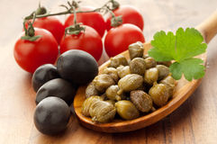 Capers olives and tomatoes over  spoon Stock Photos