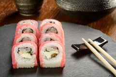 Capers rolls on slate board. Appetizing tuna, capers, shrimp and cream cheese sushi rolls, close-up. Chopsticks, a slate cheese board, a wooden table, a cast stock images