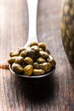 Capers in spoon on wooden background Stock Images