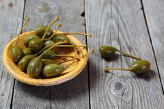 Capers in a yellow plate on a gray wooden table Stock Image