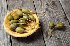 Capers in a yellow plate on a gray wooden table Stock Images