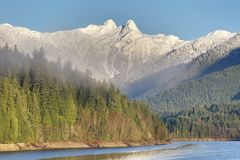 Capilano Reservoir and the Lions, Vancouver, British Columbia. A well known Vancouver scenic. The mountain peaks known as the Lions above Capilano Lake. British Stock Photos