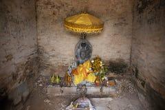 Capilla budista con la estatua de piedra de Buda debajo del paraguas amarillo con ofrendas Altar budista tradicional foto de archivo libre de regalías