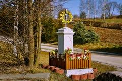 Capilla católica con las flores y las decoraciones amarillas en el fondo del campo y del camino imagen de archivo libre de regalías