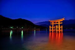 Capilla de Itsukushima encendida para arriba en la noche imagenes de archivo