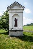 Capilla de la columna con el árbol en el fondo, el prado y el camino estrecho cerca del pueblo de Milesov en República Checa Fotos de archivo