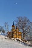 Capilla de madera en un día de invierno soleado en un cielo azul del fondo con la luna Fotos de archivo libres de regalías