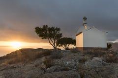 Capilla en una colina en la puesta del sol Fotos de archivo