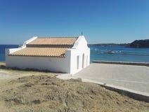 Capilla San Nicolás y playa Agios Nikolaos en fondo fotos de archivo