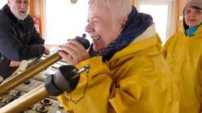 Capitán auxiliar femenino que habla al altavoz en la navegación en el panel en nave moderna Boatswain que habla con el hailer rui almacen de metraje de vídeo