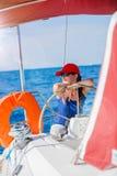 Capitán de la muchacha a bordo del yate de la navegación en travesía del verano Aventura del viaje, navegando con el niño el vaca Fotografía de archivo