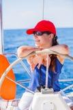 Capitán de la muchacha a bordo del yate de la navegación en travesía del verano Aventura del viaje, navegando con el niño el vaca Fotos de archivo