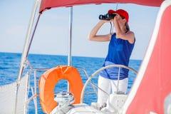 Capitán de la muchacha a bordo del yate de la navegación en travesía del verano Aventura del viaje, navegando con el niño el vaca Foto de archivo libre de regalías