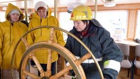 Capitán de la mujer del volante de torneado de la nave en puente de la navegación en el velero Timón de la dirección del marinero almacen de video