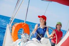 Capitán del muchacho con su hermana a bordo del yate de la navegación en travesía del verano Aventura del viaje, navegando con el Fotos de archivo libres de regalías
