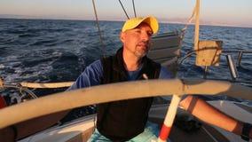 Capitão do 'yachtsman' durante a raça, em seu barco do yaht da navigação no mar esporte filme