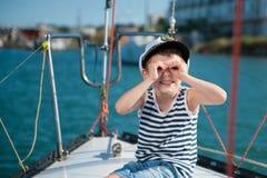 Capitão feliz do rapaz pequeno em um barco luxuoso no verão Foto de Stock Royalty Free