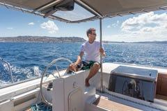 Capitão masculino atrativo que navega o veleiro extravagante do catamarã no dia de verão ensolarado na água do mar azul calma fotografia de stock royalty free