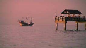 Capitão Memos Pirate Cruise e pessoa que pescam no cais 60 no fundo colorido do por do sol em praias da costa do golfo filme