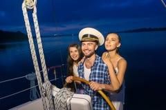Capitaine avec des filles sur le yacht Images stock