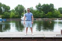 Capitaine dans le voyage de touristes En attendant le bateau au pilier homme dans des lunettes de soleil en attendant le bateau Photo stock