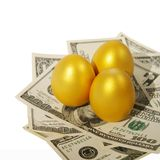 Capital. Three gold eggs on money Stock Images