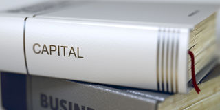 Capital - Book Title. 3D. Book Title on the Spine - Capital. Book in the Pile with the Title on the Spine Capital. Business - Book Title. Capital. Blurred Image Stock Photo