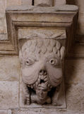 Capital in the cloister of Montmajour. France. Capital in the cloister of the Abbaye of Montmajour : a monstrous animal hold in his mouth a sinner. France Stock Image