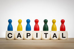 Capital concept with pawns. Capital concept: Pawns in different colors on top of toy dice Stock Photos