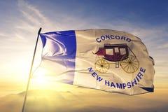 Capital da cidade da concórdia de New Hampshire da tela de pano de matéria têxtil da bandeira do Estados Unidos que acena na névo imagem de stock