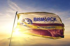 Capital da cidade de Bismarck de North Dakota da tela de pano de matéria têxtil da bandeira do Estados Unidos que acena na névoa  foto de stock