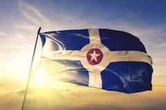 Capital da cidade de Indianapolis de Indiana da tela de pano de matéria têxtil da bandeira do Estados Unidos que acena na névoa s fotografia de stock