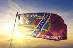 Capital da cidade de Montgomery de Alabama da tela de pano de matéria têxtil da bandeira do Estados Unidos que acena na névoa sup imagem de stock royalty free