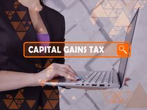 CAPITAL GAINS TAX phrase on the screen. Loan officer use internet technologies at office. Concept search and CAPITAL GAINS TAX