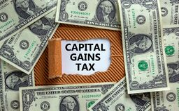 Capital gains tax symbol. The text `Capital gains tax` appearing behind torn brown paper. Dollar bills. Business and capital gai