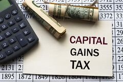 CAPITAL GAINS TAX words on a white sheet against a table with numbers, banknotes and calculator