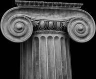 Capital iónico en fondo negro Imágenes de archivo libres de regalías