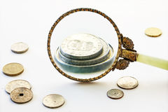Capital increase, magnifying glass enlarge a few coins, bright g Stock Photos